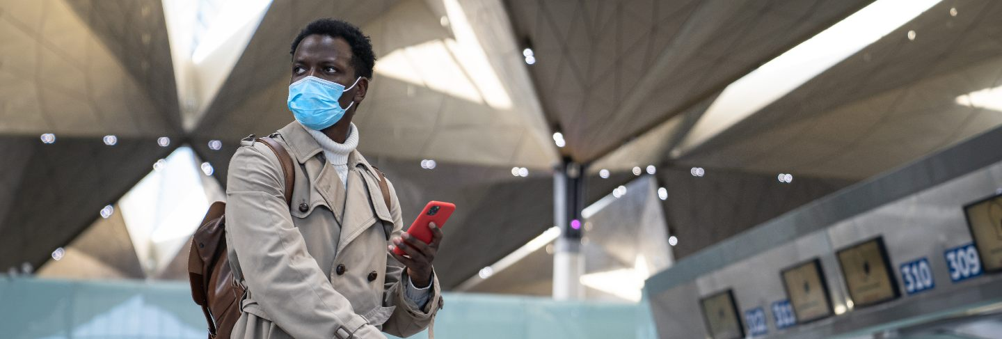 Black man standing at airport wearing face protective mask during virus epidemic, covid-19