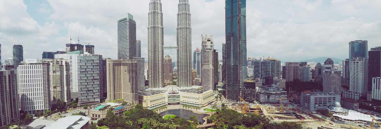 Petronas twin towers near skyscrapers and trees under a blue sky in kuala lumpur, malaysia