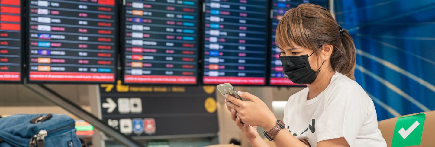 Asian female tourist wearing mask using mobile phone, searching airline flight status