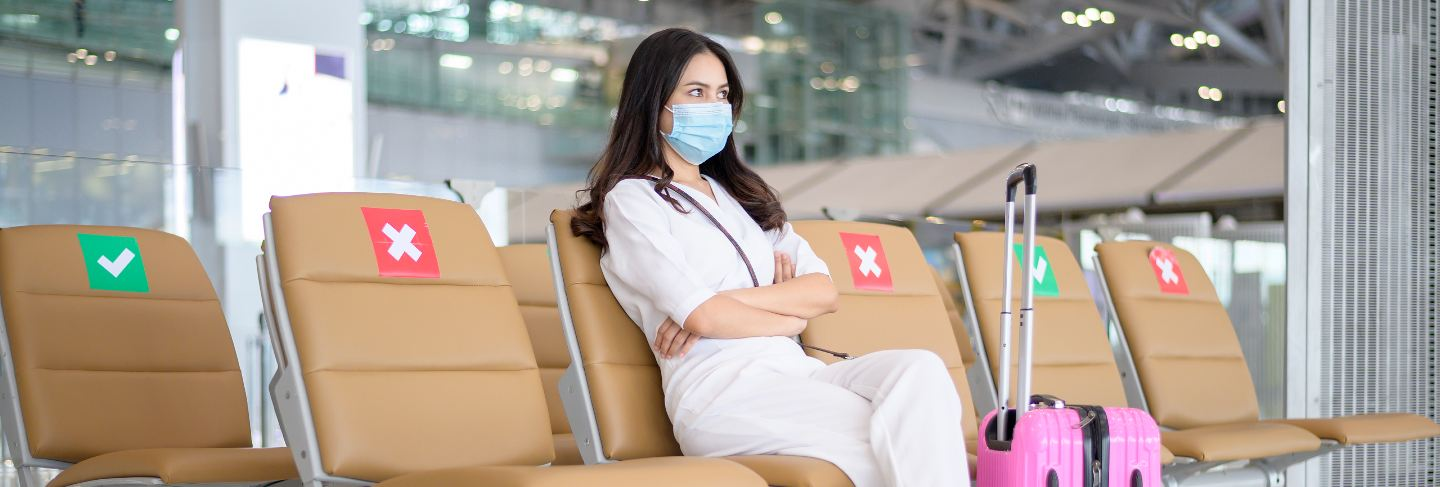 A traveller woman is wearing protective mask in international airport, travel under covid-19 pandemic