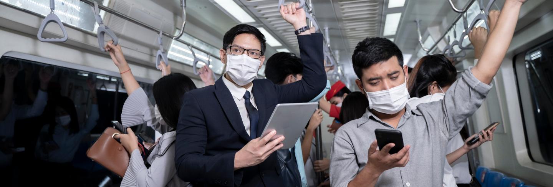 Business people standing in metro mass transit subway. man using tablet and smartphone. people wearing face mask. coronavirus flu virus in public travel.