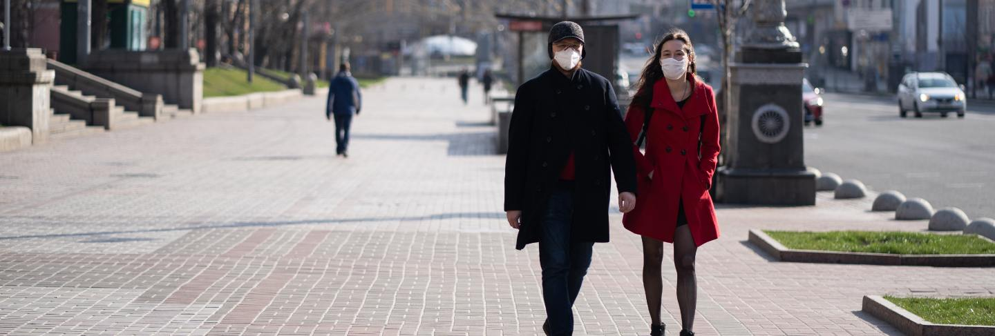 People at facial protective masks at almost empty street
