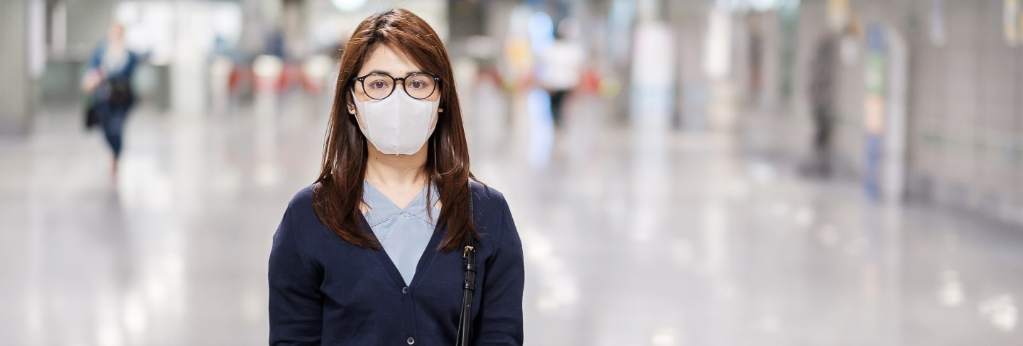 Young asian woman wearing protection mask against novel coronavirus or corona virus disease (covid-19) at airport