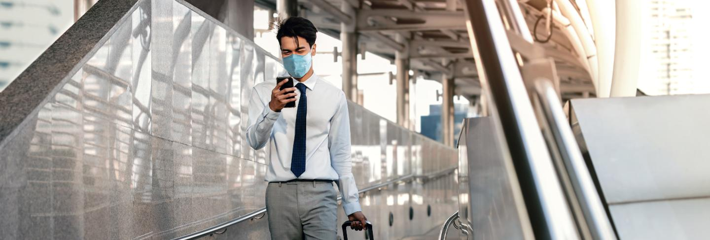 Young asian businessman wearing a surgical mask and using a smart phone while walking