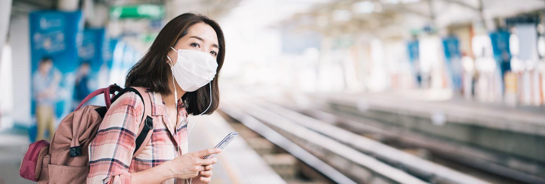 Asian woman wearing surgical face mask against novel coronavirus or coronavirus disease at public train station