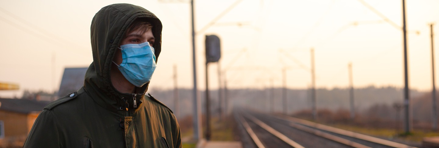 Guy in disposable medical mask standing at train station on sunset.