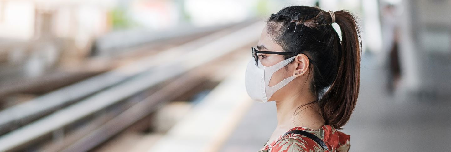 Young asian woman wearing surgical face mask protect coronavirus inflection at public train station