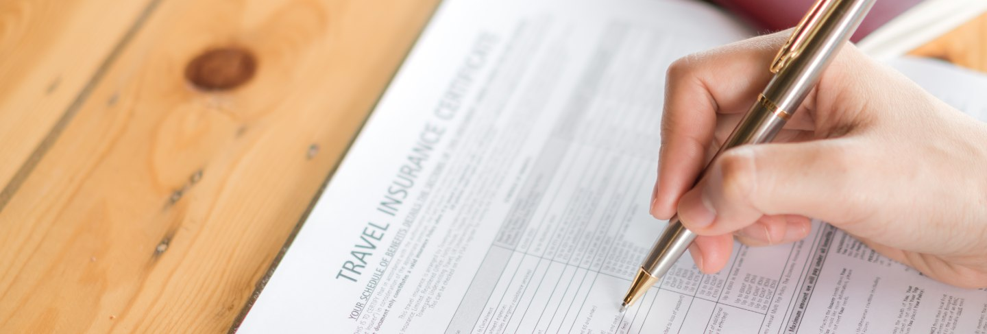 Hand with pen over travel aviation insurance application form and passport