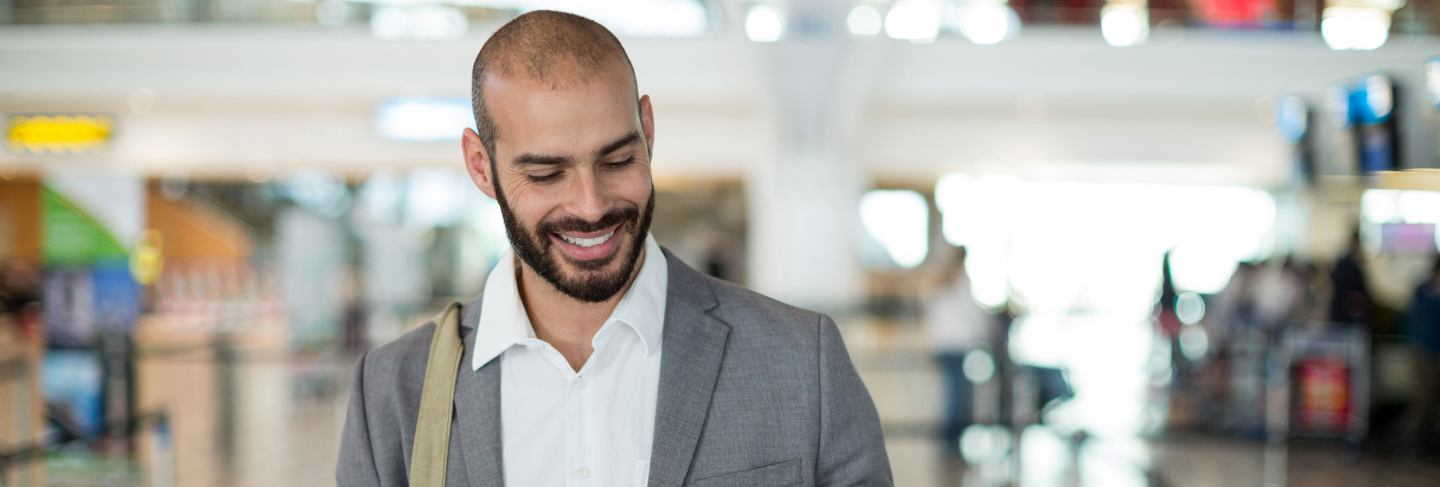 Smiling businessman holding a boarding pass and checking his mobile phone