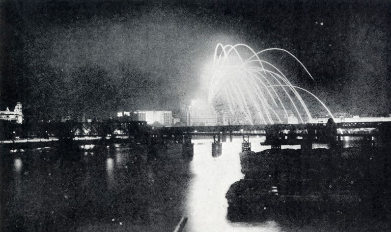 A photograph taken from Westminster Bridge on VJ night, 15th August 1945 showing fireworks soaring over the roof of buildings into the Thames