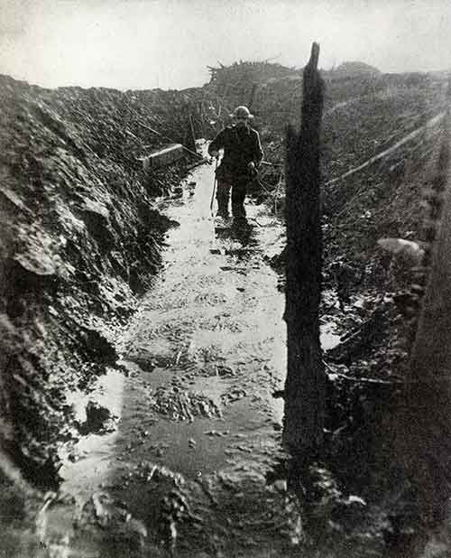 A British Army officer trudges through knee deep mud in a disused trench