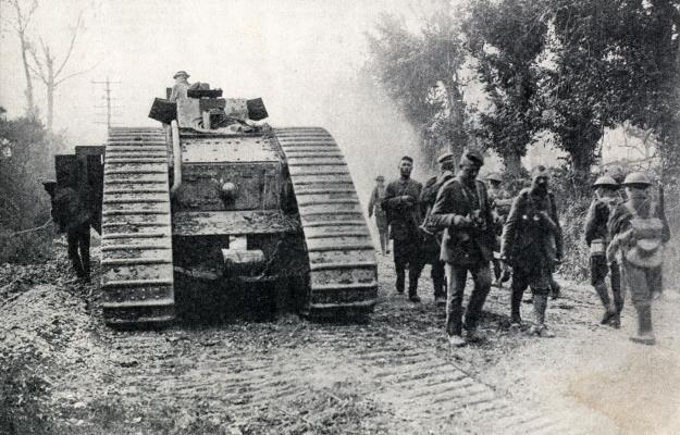 A tank on its way to the front stopped for minor adjutstment on the Amiens-Roye Road on Aug 10th 1918 being passed by German prisoners returning