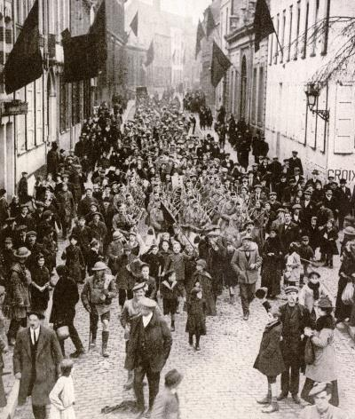 Canadian troops headed by a pipe band marching through Mons on November 11th 1918 surrounded by children men and women