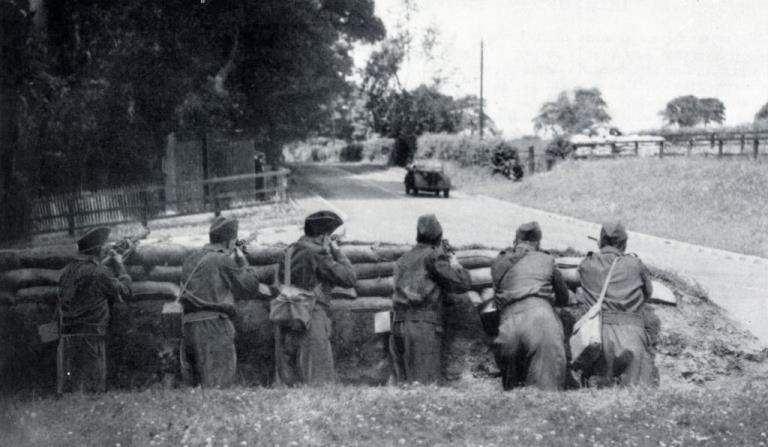 Entrenched and sheltered by sandbags men of the Home Guard have complete command of the road they survey