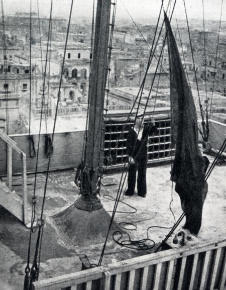 Hoisting the red flag which, with a siren, warns everyone in Malta that an air raid is imminent