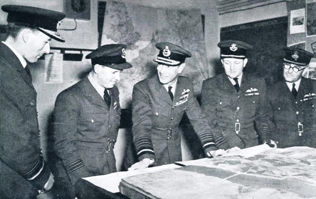 King George VI views 'Dambusters' raid photos W.C Gibson VC (second_left) Congratulated