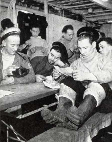 Men home from submarine patrol duty aboard a depot ship reading letters from their families and loved ones