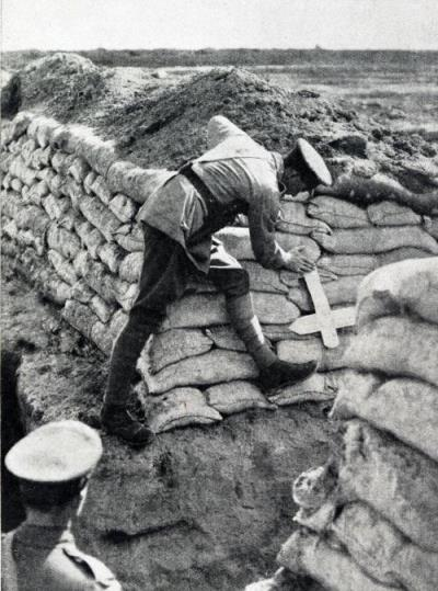 A Graves Registration Officer locating the position of a grave in the trench marked by a rough cross