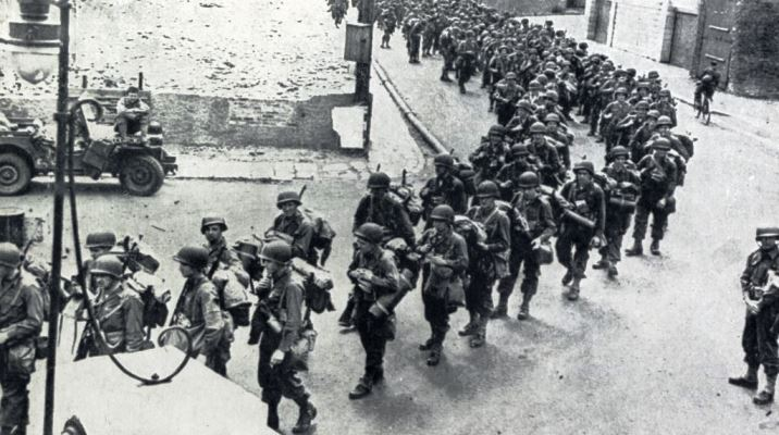 Invasion of Europe on 6th June 1944, American troops are marching to an embarkation port to take part in the initial D-Day landings