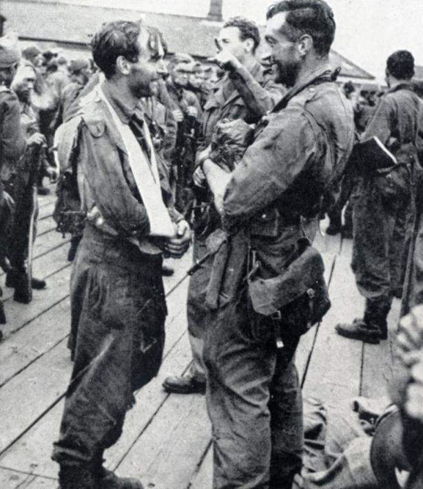 Wounded in Dieppe but undismayed, this man chats with a comrade on the quayside on arriving back in England.