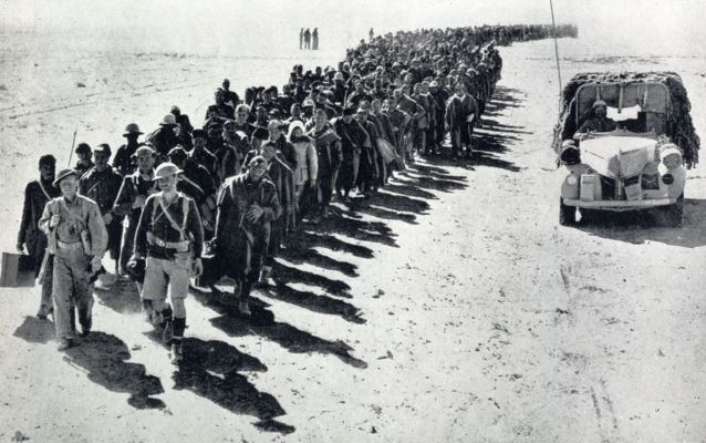 Guarded by only two soldiers a line of beaten and bewildered Italian captives are being marched to a POW Camp