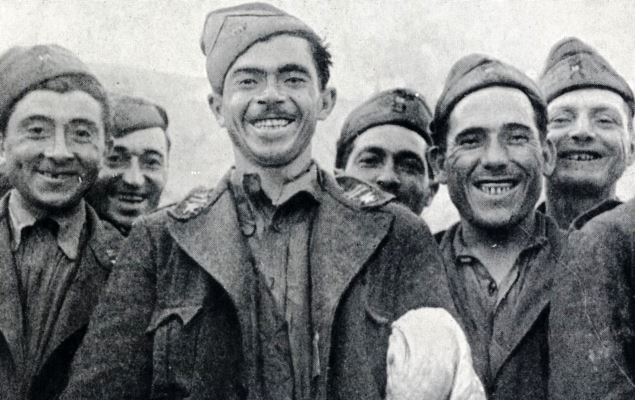 Smiling Italian POW's, only too pleased to have been taken captive, one of them still carries the symbol of surrender
