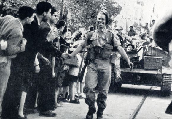 British solider's smile victory as inhabitants of Tunis give allied troops a welcome after being freed from Axis tyranny