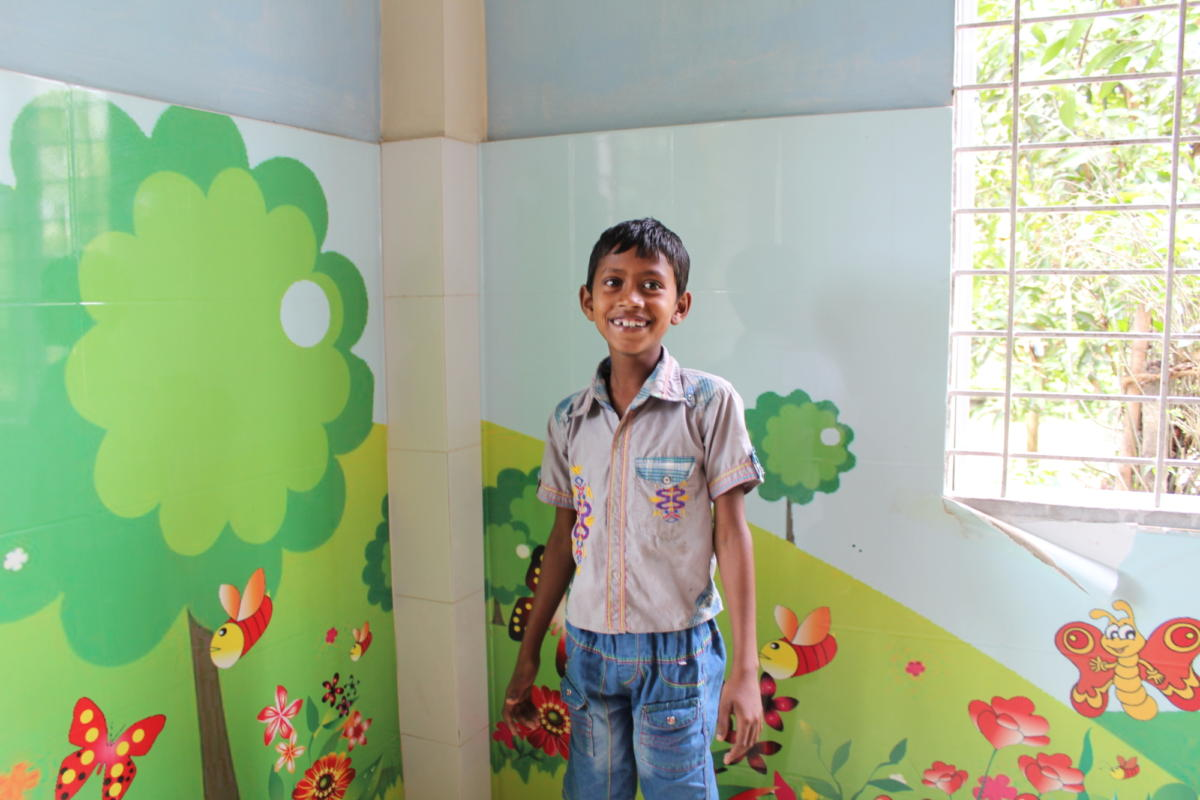 Bangladeshi paediatric patient Rafiq Bin Sayedi at the De'ep Eye Care Foundation. The room is painted with green trees and red bees, butterflies and flowers