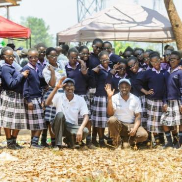 Children dressed in tartan skirts and blue jumpers, stand together at Mukinge Secondary School in Zambia during a screening
