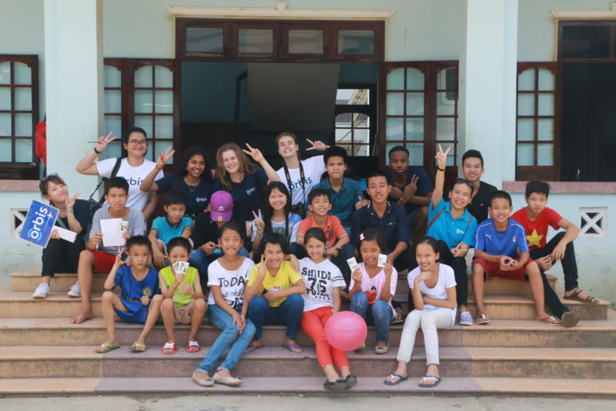 ACS students with Vietnamese schoolchildren showing the peace sign