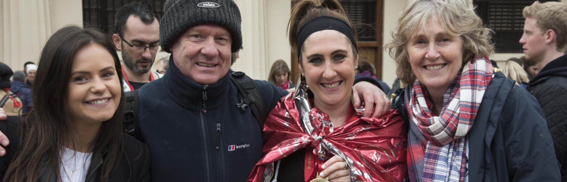 A London Marathon participant is comforted by her family and friends