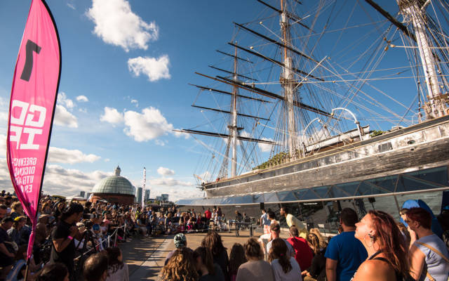 GDIF 2015, Greenwich Fair. Crowds gather round the Cutty Sark and pink flags to watch an outdoor arts show on a sunny London day.