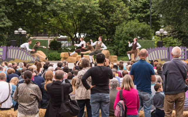 Country, Matthew Bourne's New Adventures, Dancing City, Canary Wharf, GDIF 2017. A crowd watches dancers dressed in country riding costumes dance around hay bales.