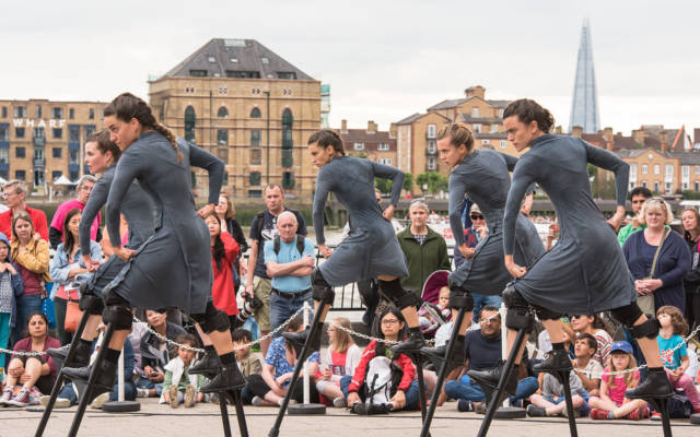 Mulier, Cia Maduixa, Dancing City, Canary Wharf, GDIF 2017. 5 women on stilts dance in front of a crowd. The shard and the river Thames are in the background.