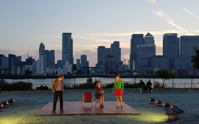 A-View-from-the-Bridge-de-Roovers, GDIF 2017. Three actors perform on an outdoor stage in Greenwich with Canary Wharf behind.