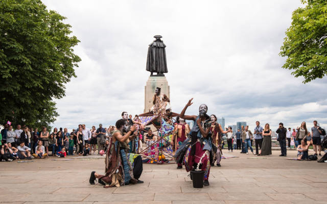 Black dancers in tribal costume perform in Greenwich Park for GDIF 2017.