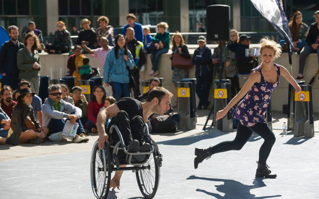 Dedicated To..., Candoco Dance Company, Dancing City, GDIF 2018. A crowd watches a dancer in a wheelchair and a dancer with one arm in Canary Wharf.