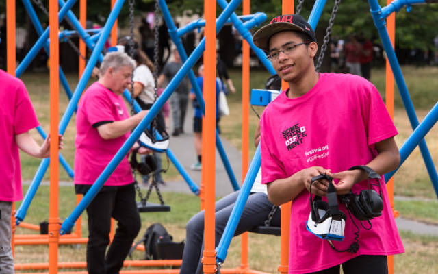 A volunteer in a pink t-shirt hands out VR headsets at Greenwich Fair, at GDIF.