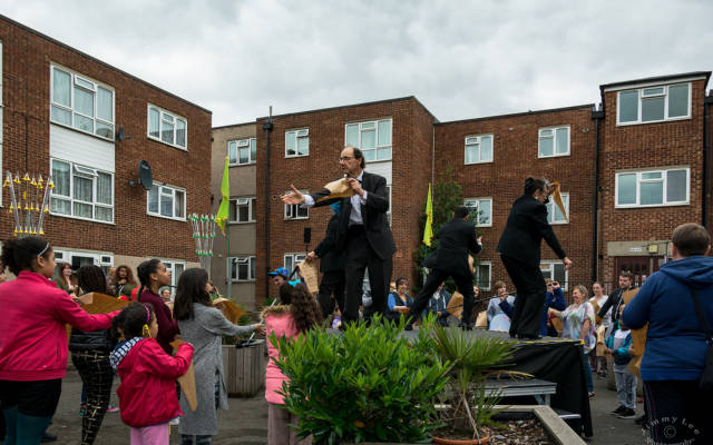 GDIF 2016. Actors in suits stand on flowerbeds in a council estate surrounded by audience.