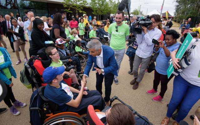 Sadiq Khan shakes hands with a man in a wheelchair, surrounded by crowds, young people in wheelchairs, and a TV camera. Festival.org.