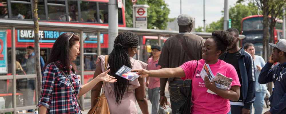 A GDIF volunteer hands out leaflets to people in Woolwich