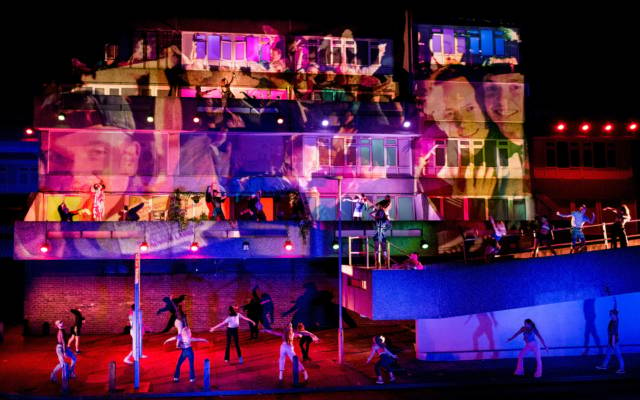 Beautiful Thing, Festival.org, Robbie Graham, GDIF 2018, Thamesmead. A concrete building is lit up with projections, dancers surround it and dance on the balconies.