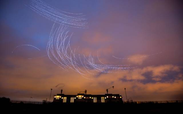 Fly by Night, Duke Riley, LIFT, GDIF 2018. Lights swirl above a building in a sunset sky in Thamesmead, created by pigeons.