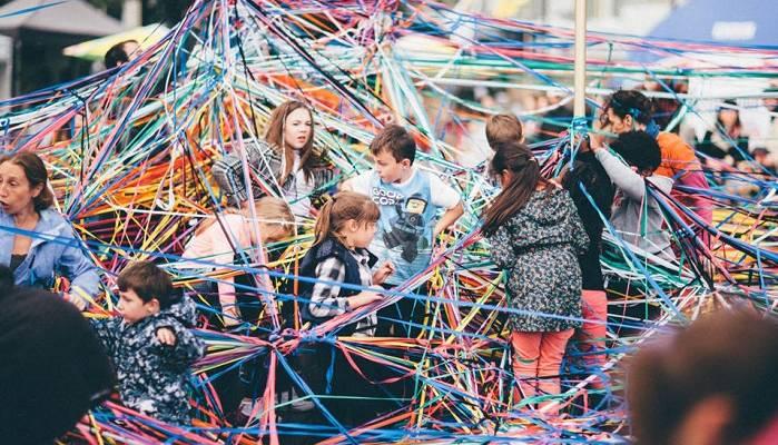 Tangle, Polyglot, Global Streets. Children play among tangled coloured string.