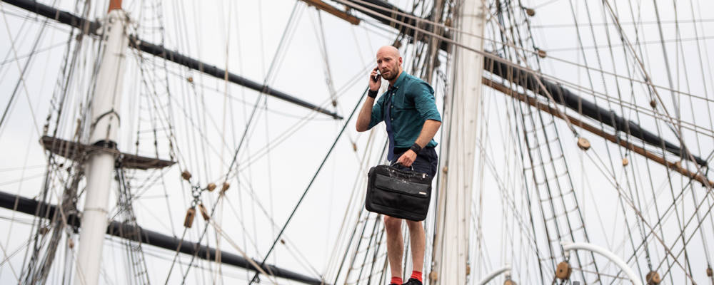 Greenwich Fair as part of Greenwich+Docklands International Festival, London, UK, 2019. A man stands on a high pole against the Cutty Sark holding a briefcase and a mobile phone.