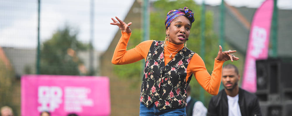 846 Live, RDLAC Sports Court, 12th September 2020. A black actor in an orange top gesticulates. In the background is another actor, audience members wearing face masks, and a pink GDIF banner.