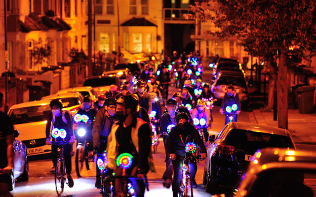 Lullaby by Luke Jerram in Plumstead at GDIF 2020. A crowd of people ride bikes covered in fairy lights along a residential street.
