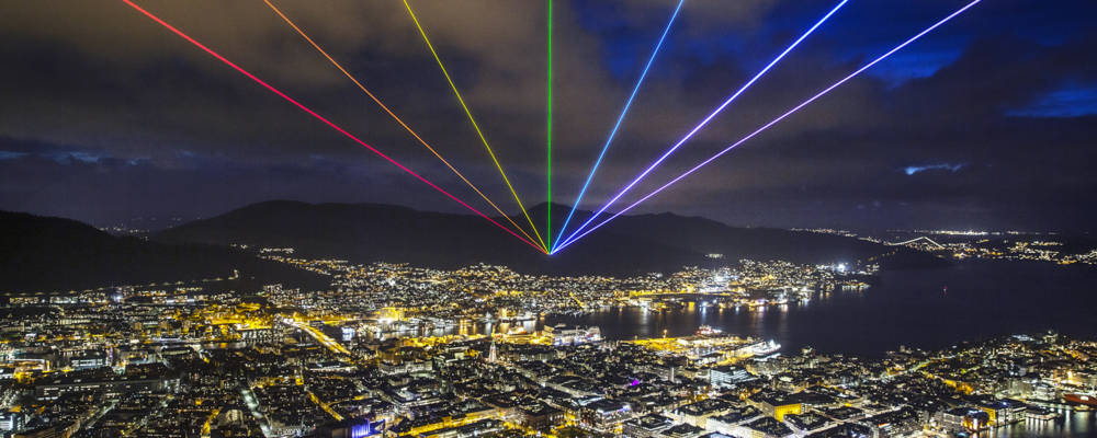Global Rainbow, Yvette Mattern. Global Streets 2021. A laser rainbow shines out over an illuminated nighttime cityscape.