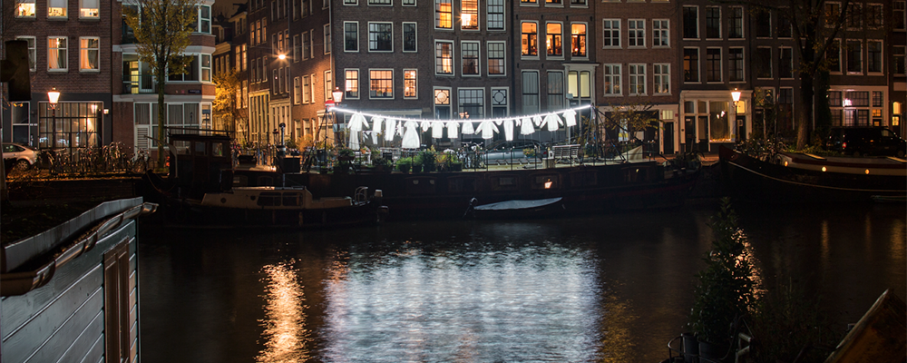 Neighborhood, Sergey Kim, Light Art Collective. Global Streets 2020, Liverpool. An illuminated laundry line hangs in front of a building, lighting up the river below.