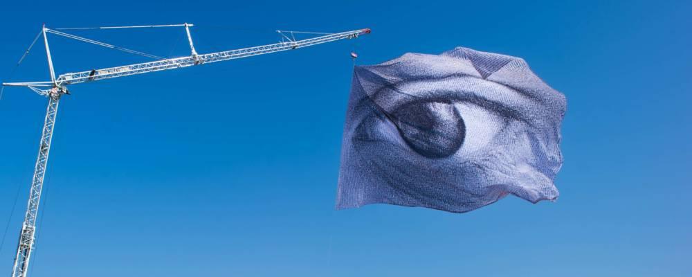 DanAcher_WeAreWatching_Greenwich_GDIF_2021. A flag with a giant eye prinetd on flying against a blue sky.
